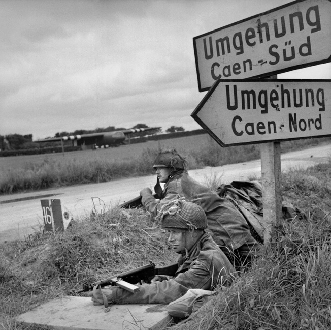 Partially concealed in a ditch, glider troops of the 6th Airborne Division guard a crossroads near Ranville on June 7, 1944. Their glider is seen across the road where it landed the previous day.