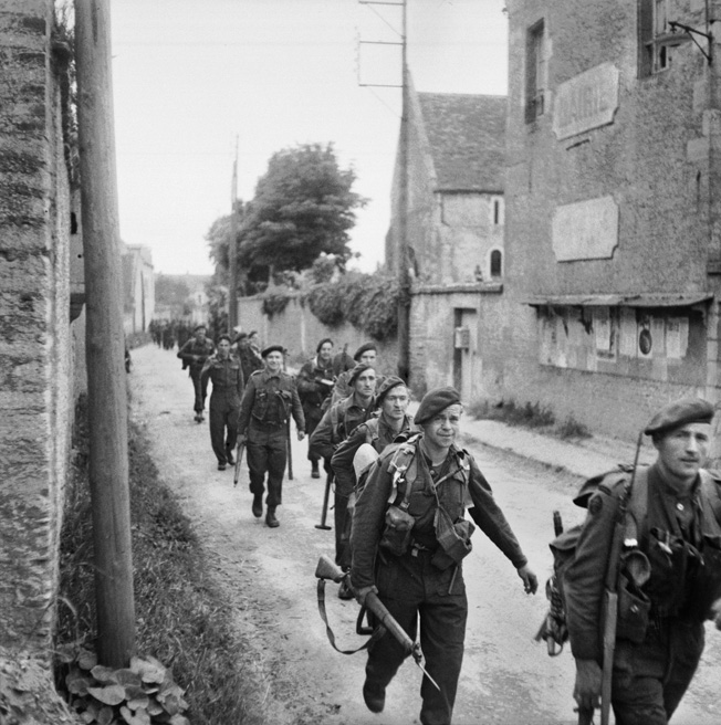 The airborne troops holding Pegasus Bridge were instructed to hold until relieved. These Royal Marine Commandos march through the town of Colleville-sur-Orne en route to the bridge and the relief of the lightly armed airborne soldiers.