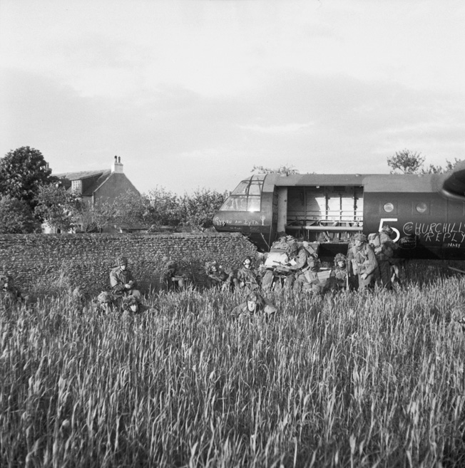 Glider troops of the 6th Airborne Division assemble near their wrecked glider in a field outside the town of Ranville. Moments earlier, the glider had careened through a stone wall during landing. Many of the casualties sustained by the glider troops were due to rough landings.