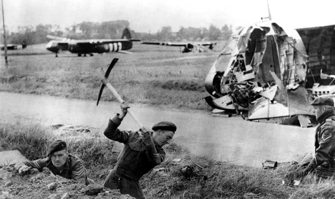 Royal Marine Commandos dig trenches and prepare defensive positions near Pegasus after relieving the glider troops who had taken Pegasus Bridge across the Caen Canal hours earlier. Several of the gliders used by the airborne troops are visible in this photo, and the damage to the nose of one of the aircraft is prominent.