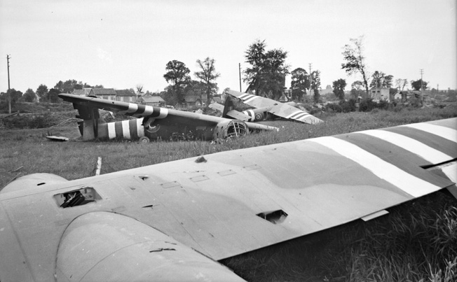Horsa gliders that transported British airborne troops to their D-Day objective, the bridge over the Caen Canal, lie broken in a field adjacent to the bridge. The glider pilots made their landings with pinpoint accuracy.