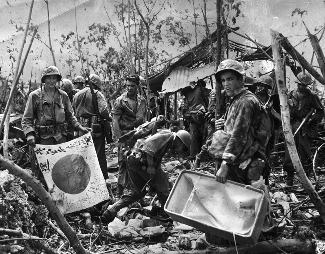 Gathering souvenirs after overrunning a Japanese command post on Peleliu, u.S. Marines reflect the strain of intense combat in their faces. Japanese flags, often emblazoned with slogans and good wishes from the home town of enemy soldiers, were highly prized.