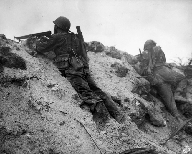 Peering cautiously from the cover of an embankment on Peleliu, a U.S. Marine raises his Thompson submachine gun while a companion scans the horizon in another direction.