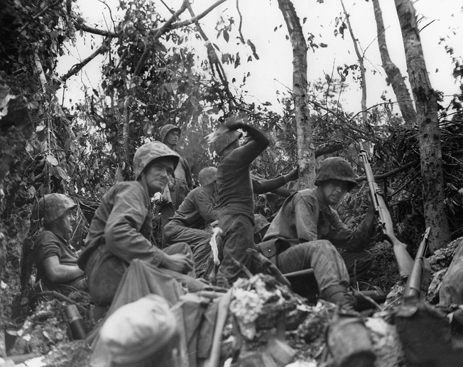 """During one of many close quarters engagements in the dense jungle of Peleliu, Marines hurl molotov cocktails towards enemy positions along a bitterly contested elevation nicknamed """"Suicide Ridge."""""""
