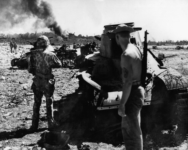 """Marines commanded by Colonel Lewis B. """"Chesty"""" Puller advance along a ridge on Peleliu after driving off the Japanese defenders and destroying two of their light tanks."""