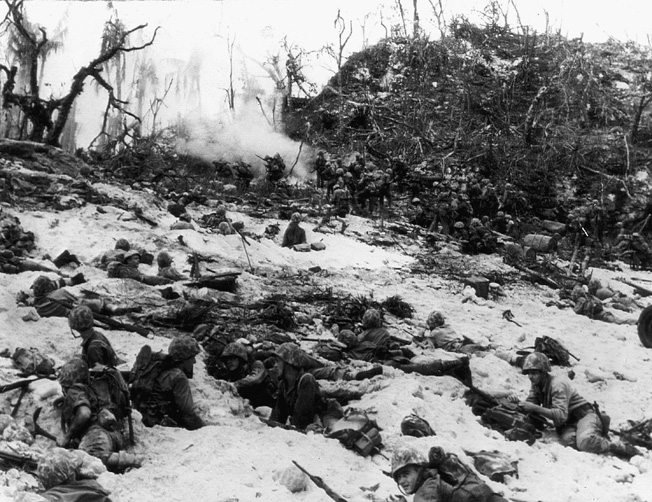 Under heavy fire from an underestimated enemy, Marines of the 1st Division dig in and await orders to move forward.