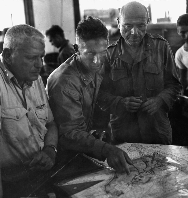 Maj. Gen. Roy S. Geiger (left), commander of the III Marine Amphibious Corps, and Maj. Gen. William H. Rupertus, commander of the 1st Marine Division (right) carefully study a map during operations planning.