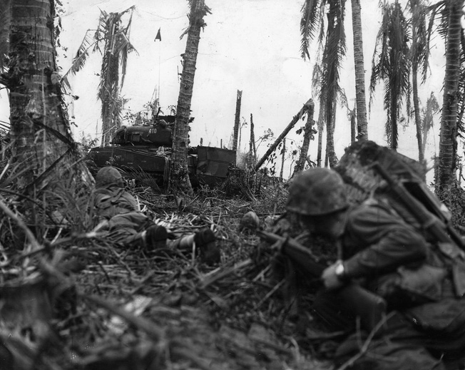Two Marines crouch low, while cautiously making their way towards a Japanese stronghold.