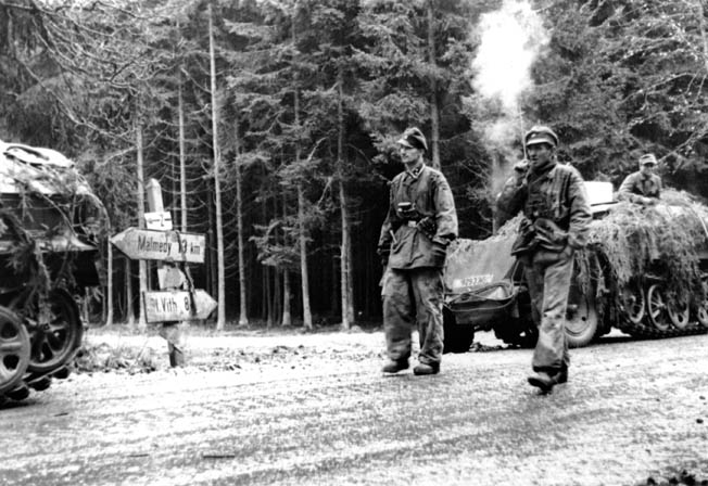 Smoke from his cigar curls upward as an SS officer and his detachment pause at a road sign directing traffic toward the village of Malmedy, Belgium, during the opening hours of the German Ardennes offensive that came to be known as the Battle of the Bulge. In a field near Malmedy, troops under the command of SS Colonel Jochen Peiper committed one of the most infamous battlefield atrocities of World War II.