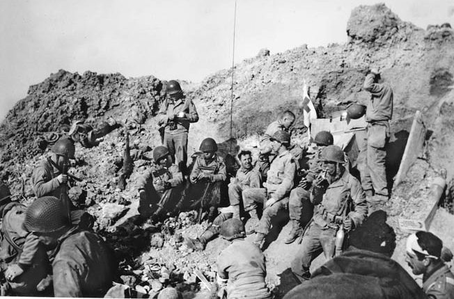 After taking the heights at Pointe-du-Hoc, scene of numerous bunkers, U.S. Rangers enjoy a break in one of the enormous shell craters being used as an aid station. However, the guns they were expecting to capture were not there.
