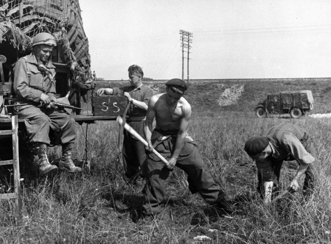 Digging in to hold their position somewhere in Normandy, some of these Polish soldiers have stripped to the waist in the summer heat.