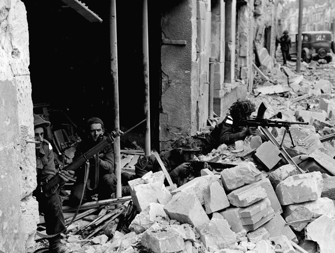 Attempting to pinpoint the locations of German snipers hiding on the upper floors of nearby buildings, Canadian soldiers take cover amid the ruins of the embattled town of Caen.
