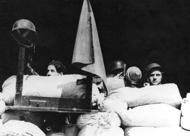 Manning a barricade in a Prague street, Czech Resistance members brandish captured German weapons. The revolt against Nazi rule began at 3 PM on May 5, 1945.