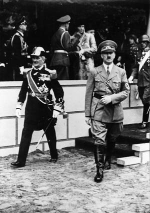 Resplendent in the uniform of a Hungarian Navy admiral, Nicholas Horthy strides with Adolf Hitler from a platform after a formal event. The pragmatic Horthy commanded respect from Hitler and received greater latitude than other nominal heads of state who served the Nazis.
