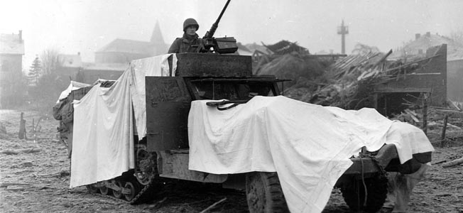 Makeshift camouflage provided by bed- sheets is shown on this American half-track on the outskirts of Bastogne in December 1944.