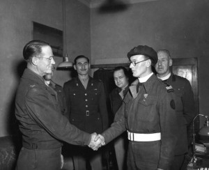 Colonel C.W. Christenberry shakes the hand of Captain Albert E. Basil (right) after awarding him the Silver Star for gallantry in action with the American Armed Forces.