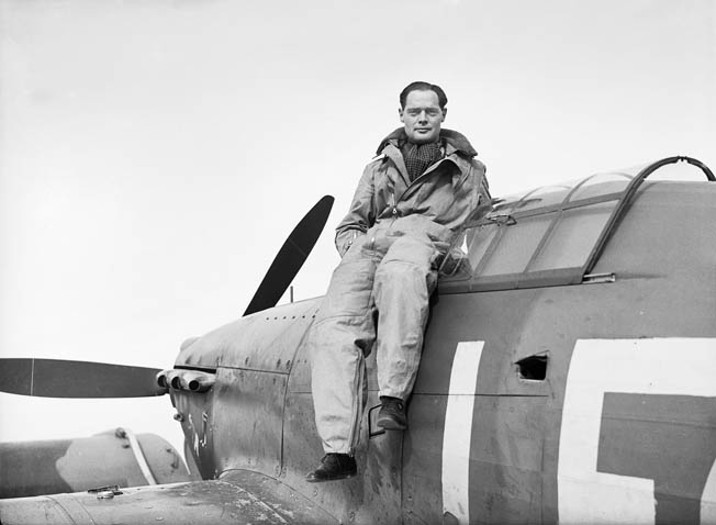 Squadron Commander Douglas Bader sits on the edge of the cockpit of his Hawker Hurricane fighter.