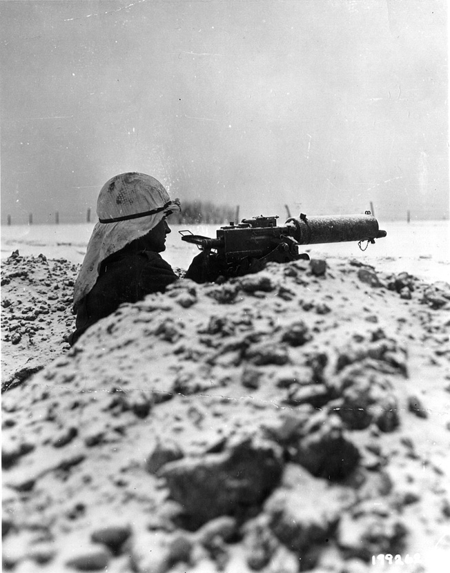 Wearing part of a sheet as camouflage, an American soldier mans a Browning .30-caliber machine gun on the outskirts of the embattled town of Bastogne.