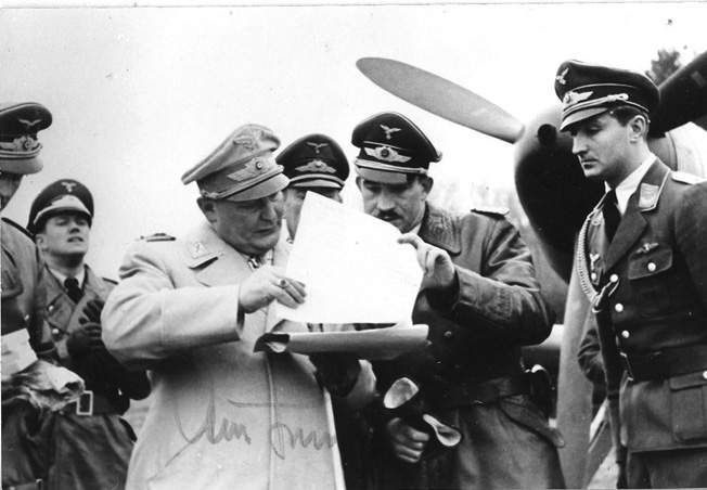 Reichsmarshal Hermann Göring, chief of the Luftwaffe, stands at left while conferring with Adolf Galland during an inspection of Galland's former fighter command in 1941.