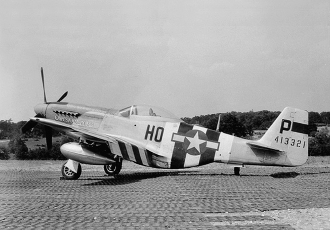 Painted in alternating black and white D-Day invasion recognition stripes, the P-51 Mustang that Major George Preddy flew while scoring most of his kills sits on a runway. Preddy's planes were named Cripes A'Mighty, a reference to his favorite exclamation while gambling.
