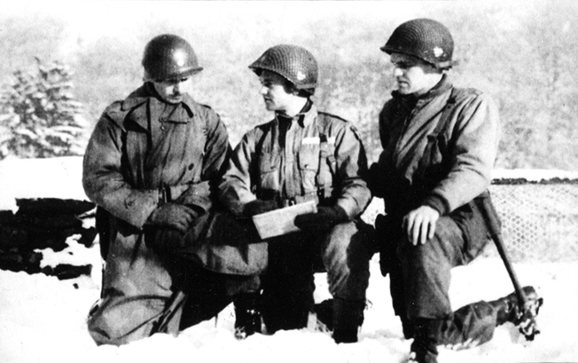 Conferring with other officers of the U.S. 101st Airborne Division near Bastogne, John Hanlon, then holding the rank of major, kneels in the snow at right to survey a map.