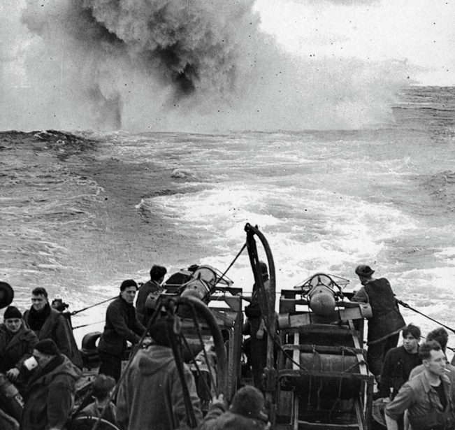"""A plume of water shoots skyward as a German U-boat is struck by a barrage of depth charges and """"Hedgehog"""" bombs."""