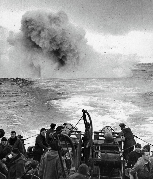 "A plume of water shoots skyward as a German U-boat is struck by a barrage of depth charges and ""Hedgehog"" bombs."