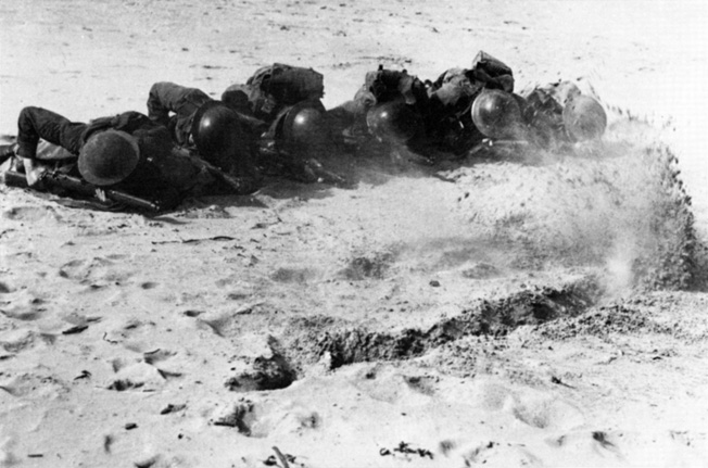 Commandos crawl through bullet-ridden sand during a training exercise at the Commando Training Center at Achnacarry, Scotland. Father Basil first met the Rangers when they arrived at the center in 1942.