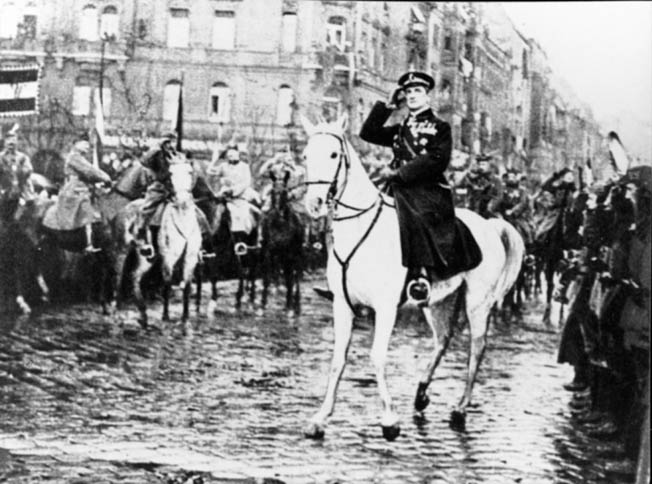 Admiral Nicholas Horthy astride his white horse greets an approving throng following the victory of his anti-communist Hungarian Army of Liberation, which defeated a leftist uprising led by Bela Kun in 1919. Horthy, already a war hero, was also elevated to the post of regent of Hungary.