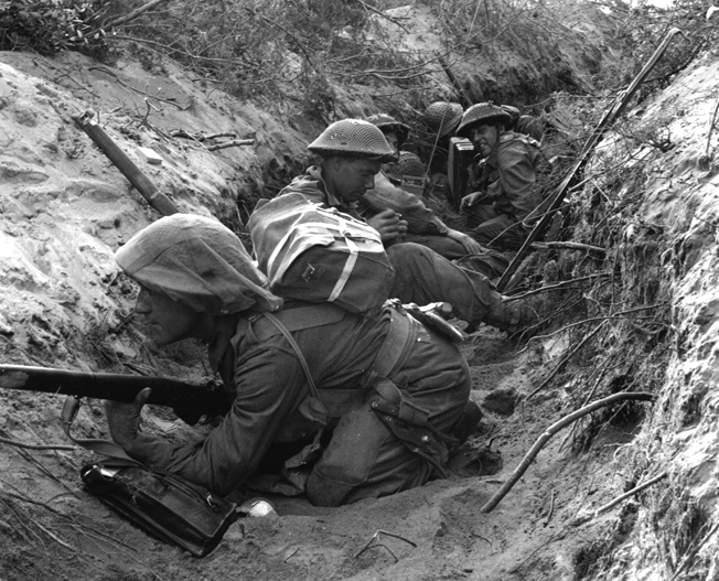Occupying a captured German communications trench, soldiers of D Company. 1st Battalion, Green Howards prepare to move out during offensive operations at Anzio, Italy, on May 22, 1944.