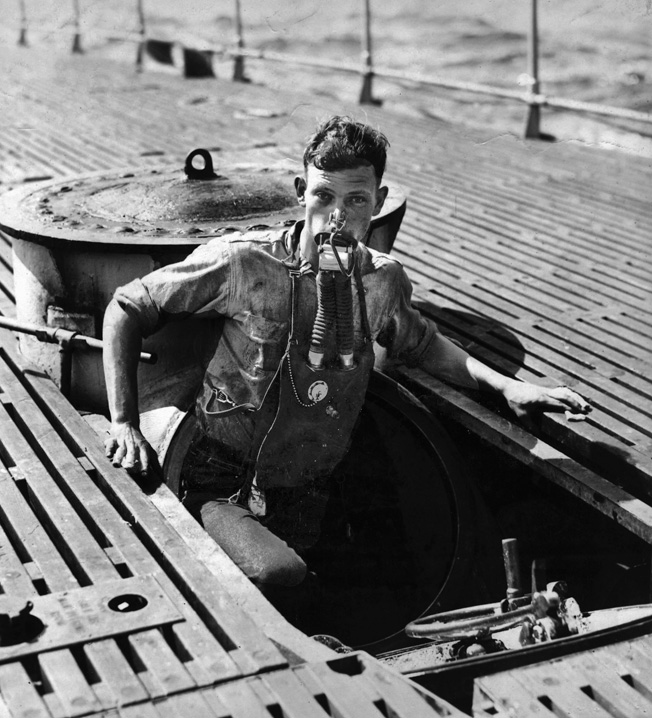 "030808-N-0000X-001 Navy File Photo -- USS V-5 (SC 1) crewman A. L. Rosenkotter exits the submarine's escape hatch wearing the ""Momsen Lung"" emergency escape breathing device during the submarine's sea trials in July, 1930. The emergency breathing device was named for its inventor, U.S. Navy submarine rescue pioneer Cdr. Charles ""Swede"" Momsen. The submarine V-5 was later renamed USS Narwhal (SS 167). U.S. Navy photo. (RELEASED)"