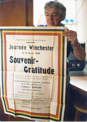 Joan Hanlon, John's widow, displays a welcoming banner that was produced by the people of Bastogne to commemorate his postwar visit.