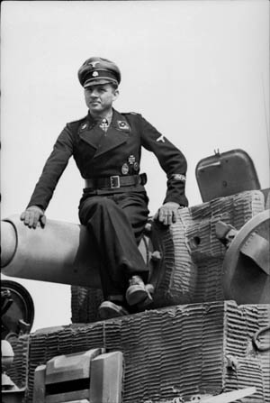 Seated atop the 88mm cannon of his Tiger I heavy tank, Obersturmführer Michael Wittmann sports the Knight's Cross with Oak Leaves at his throat. The oak leaves were awarded to the Tiger ace on January 30, 1944, following an impressive combat record on the Eastern Front.
