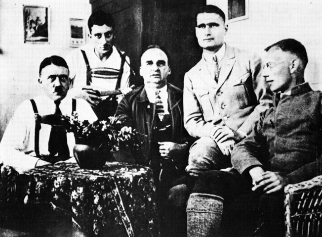 While incarcerated in Landsberg prison, Hitler poses with Hess, his trusted secretary, and three other Nazis. Hitler's time in prison was something less than oppressive. The guards were Nazi sympathizers and allowed him to have numerous visitors and flowers in his cell.