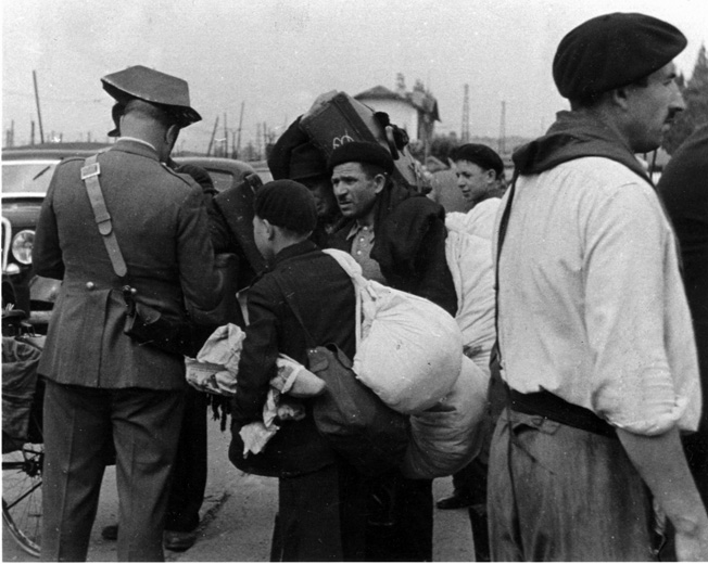 A Spanish police officer examines papers at a border crossing in 1940.