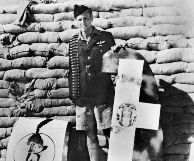 Beurling poses with the rudder and unit emblem cut from a crash-landed Italian Macchi MC.202 fighter of 378ª Squadriglia/51º Stormo CT, one of four enemy aircraft he shot down over Gozo, Malta's sister island, on July 27, 1942.