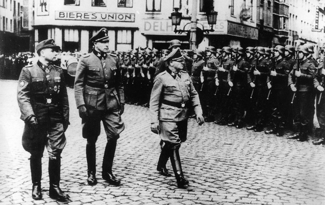 LEON DEGRELLE (1906-1994). Belgian Nazi Commander Leon Degrelle (left) with SS General Sepp Dietrich and General Richard Jungclaus reviewing Walloon troops in Charleroi, Belgium, 1941.
