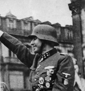 Bedecked with medals and a steel helmet, SS Sturmbannführer (Major) Leon Degrelle raises the Nazi salute on April 12, 1944.