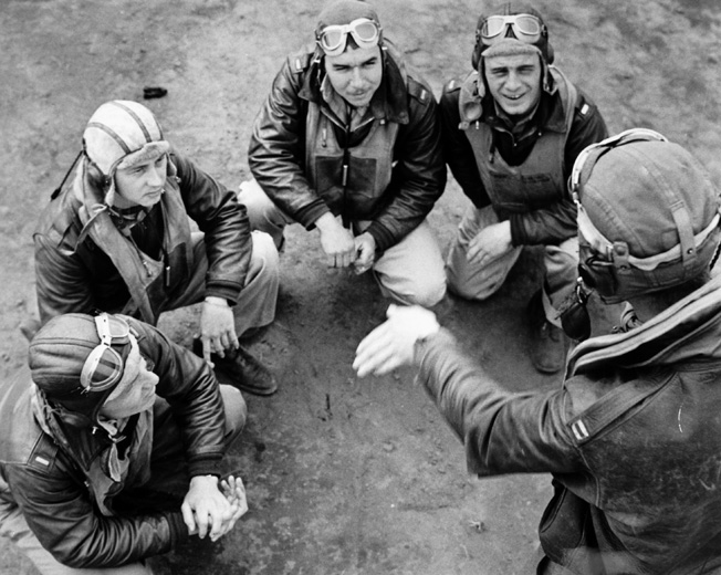 "A group of Flying Tigers discusses an upcoming mission. Recognizing their P-40s could not outmaneuver the Japanese fighters, Chennault instructed his flyers to use unorthodox hit-and-run tactics. ""Use your speed and diving power to make a pass, shoot, and break away,"" he told his men."