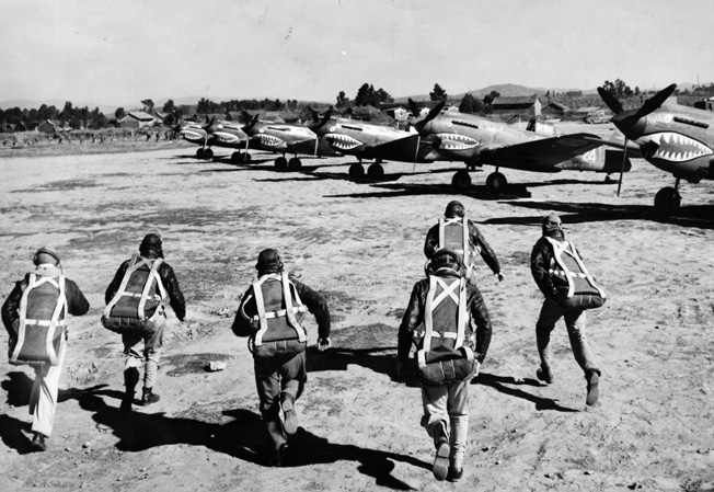 Alert to a coming Japanese air raid, American pilots rush to their P-40s parked at the read on a Chinese airfield.