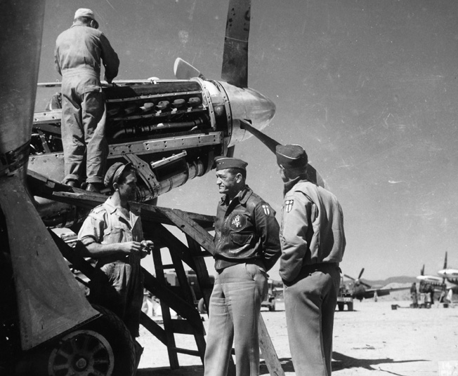 Later in his career, General Claire Chennault commanded the U.S. Fourteenth Air Force. Here, he is shown talking with a sergeant who is working to repair a fighter plane engine at an airstrip somewhere in China.