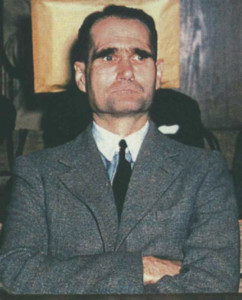 A gaunt Rudolf Hess sits in a courtroom at Nuremberg in 1946, surrounded by former Nazis on trial for war crimes.