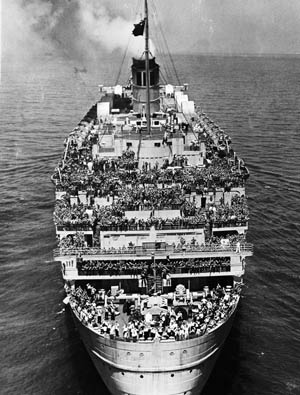 In this photo taken on June 20, 1945, from a hovering U.S. Coast Guard helicopter, the decks of the Queen Mary are packed with 14,000 American soldiers straining to gain a glimpse of the New York City skyline upon their return home from Europe.