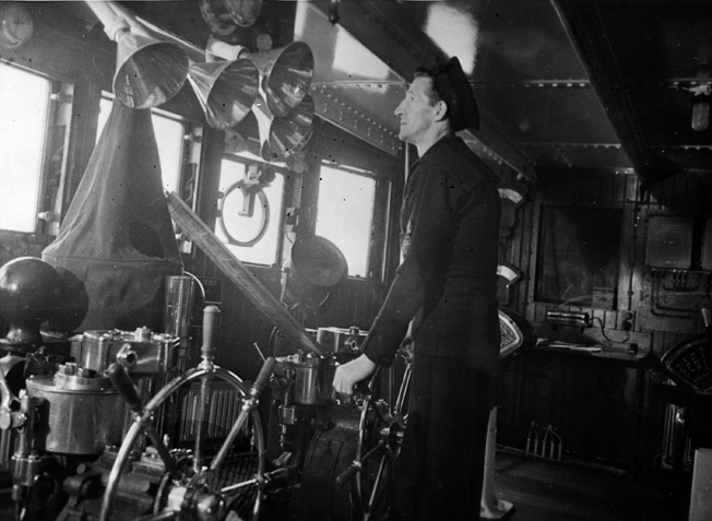 A veteran of the Queen Mary since her maiden voyage, Quartermaster William Hilton stands at one of the ship's two wheels inside the large wheelhouse.
