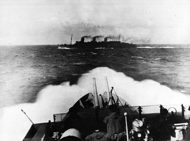 Seen from the bridge of the escorting British cruiser HMS Scylla, the Queen Mary slices through the waters of the Atlantic. During an unfortunate accident, the great liner collided with a Royal Navy warship, which quickly sank.