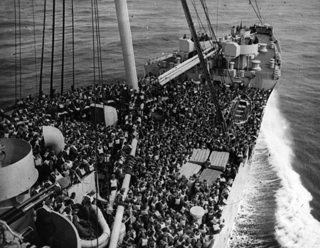 Troops crowd the deck during a lifeboat drill aboard the Queen Mary in December 1944. The luxury liner churns the sea swiftly, her captain and crew wary of the threat of German U-boats.