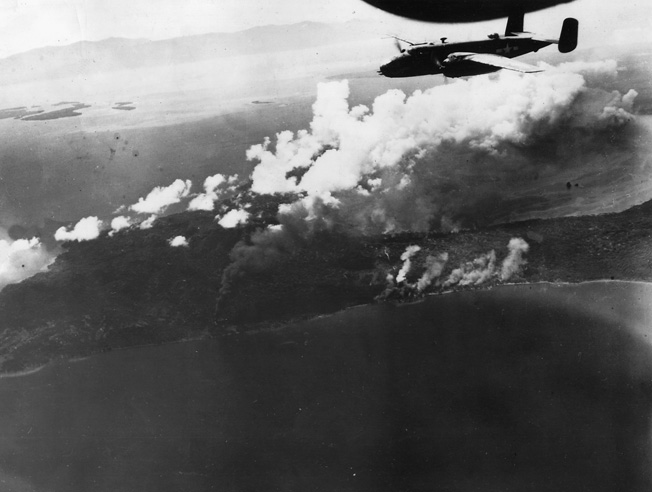 A B-25 Mitchell of the 13th Air Force roars above burning Japanese oil installations in New Britain.