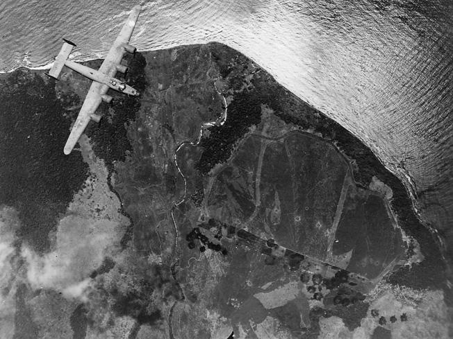 A B-24 of the 5th Air Force flies over the Japanese airfield at Cape Cloucher, New Britain.