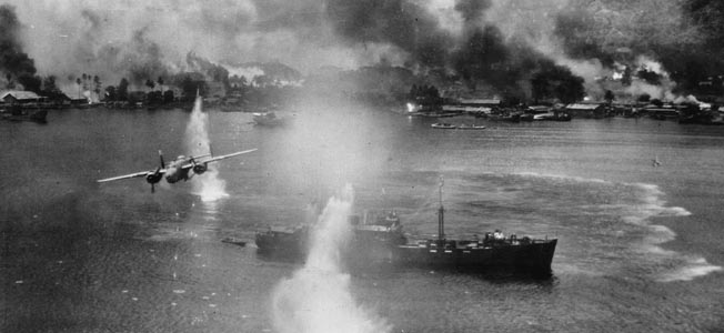 A pall of black smoke hangs over the shore installations at Rabaul as a B-25 medium bomber streaks above a Japanese merchant ship riding at anchor.