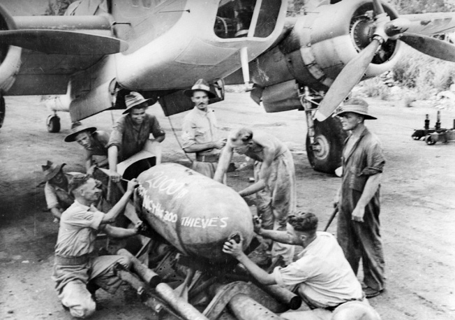 "Members of an RAAF squadron leave their mark on a 2000-pound ""daisy cutter"" to be dropped on the Lakunai Aerodome in Rabaul."